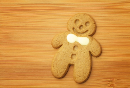 Gingerbread man cookie on wooden background photo
