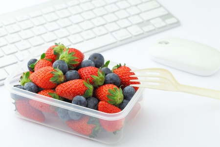 plactic: Health lunch with strawberry and blueberry mix in office Stock Photo