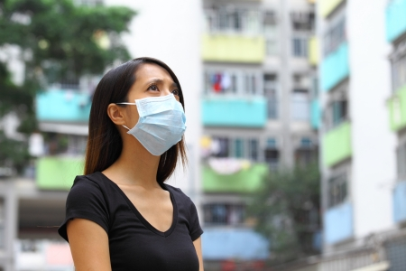 dust mask: Woman wearing medical face mask in crowded city Stock Photo