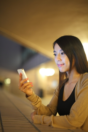 woman using phone in city at night  photo