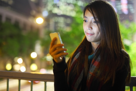 woman use mobile phone in city at night photo