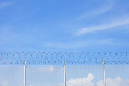 Chain link fence with barbed wire under blue sky photo