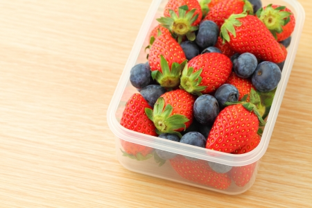 Strawberry and blueberry mix in plastic container photo