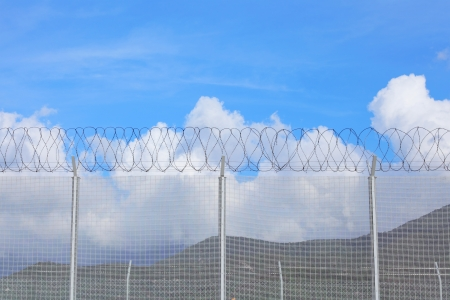 enclosures: Chain link fence with barbed wire under blue sky