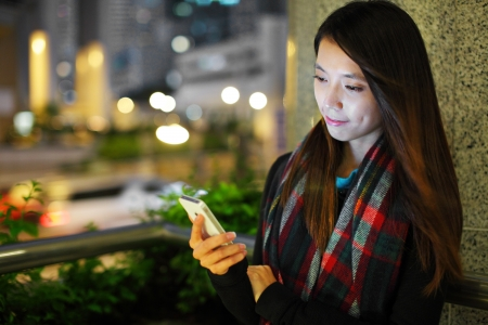 busy street: Woman using smartphone in city at night
