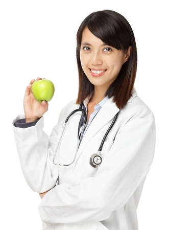 Asian female doctor holding green apple photo