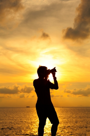 Silhouette photographer at sunset photo