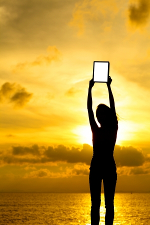 Silhouette of woman holding tablet computer at sunset photo