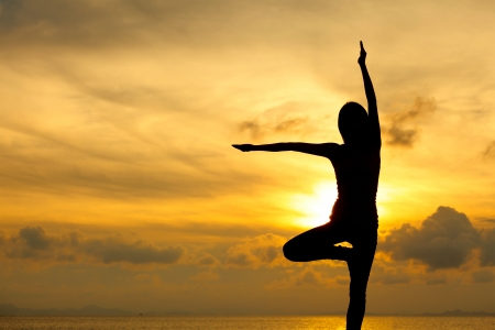 Silhouette of a woman yoga on sea sunset photo
