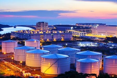 refiner�a de petr�leo: Dep�sito de aceite durante el atardecer Foto de archivo