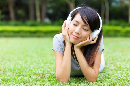 lain: Asian woman listen to song lying on grass Stock Photo