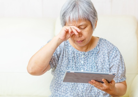 tired eyes: Asian old woman using digital tablet with tired eyes Stock Photo