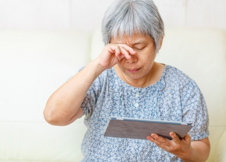 sore eye: Asian old woman using digital tablet with tired eyes Stock Photo