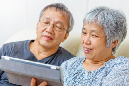 Asian elderly couple using digital tablet photo