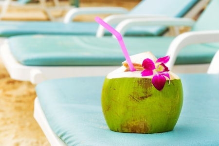 Coconut with drinking straw on beach bench photo