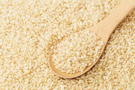 teaspoon: Brown rice on wooden teaspoon Stock Photo