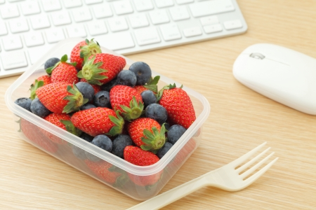 Berry mix lunch box in working desk photo