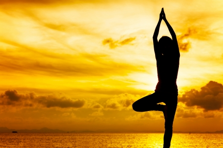 Woman doing yoga at sunset time photo