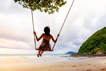 columpio: Muchacha que juega el oscilaci�n en la playa