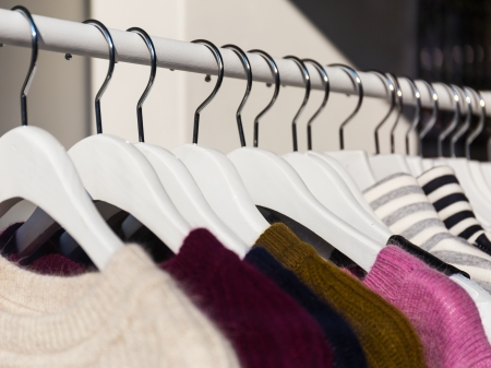 clothing rack: Clothes hang on a shelf in a store Stock Photo