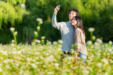 korean woman: Asian couple take shot by mobile phone Stock Photo
