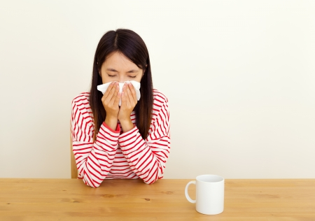 Asian woman sneezing at home Stock Photo