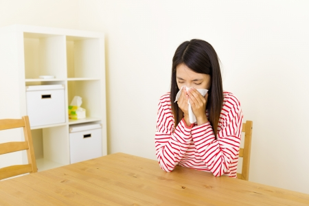 Asian woman sneezing at home  photo