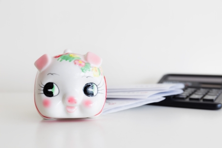 Piggy bank, calculator and statement photo