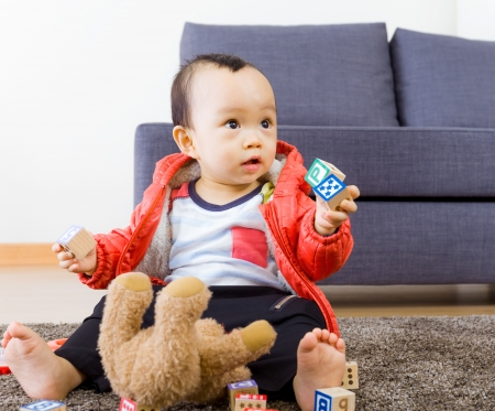 Asian baby boy playing toy block at home photo