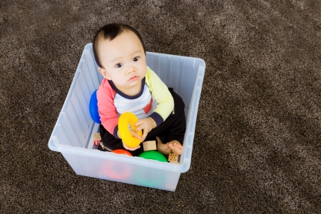 Asian baby boy playing inside the plastic box photo