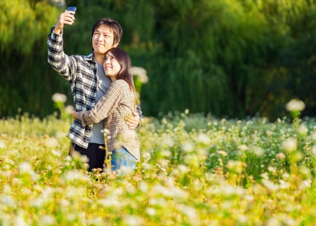 retratos: Asia pareja toma la foto con el tel�fono m�vil
