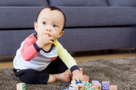 Asian baby boy with fingers in mouth at living room photo