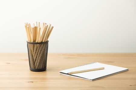 Pencil in pot with notebook photo