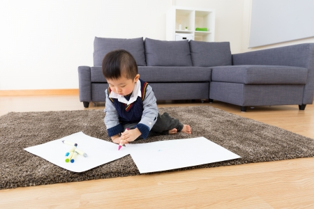 Asian baby boy drawing picture at home photo