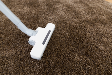 Brown carpet with vacuum cleaner in living room  photo