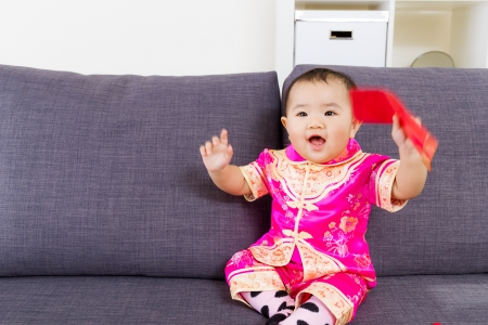 Asian baby holding red pocket with traditional chinese clothing photo