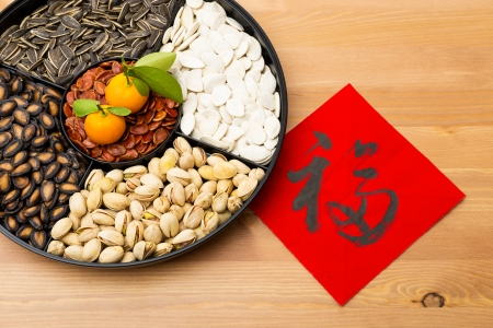 Traditional Lunar new year snack tray and chinese calligraphy, meaning for blessing good luck  Stock Photo