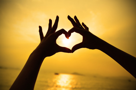 Silhouette hand in heart shape during sunset photo