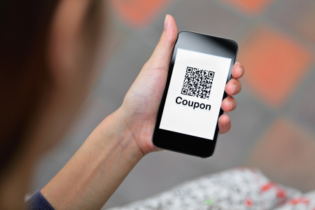 Coupon QR code on smart phone  Stock Photo