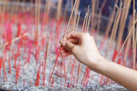Offering incense stick to god in Chinese temple photo
