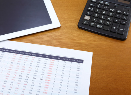 Office table with tablet, calculator and data chart photo