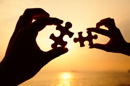 fit on: Hombre y mujer manos tratando de conectar las piezas del rompecabezas