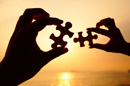 Man and woman hands trying to connect puzzle pieces  photo