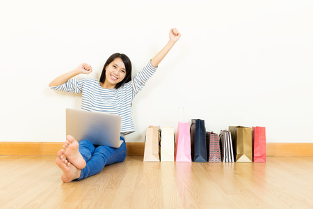 Asian woman online shopping at home with assorted paper bag photo