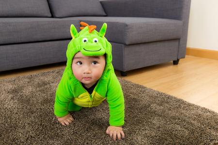 bebe gateando: Bebé joven vestida de dinosaurio