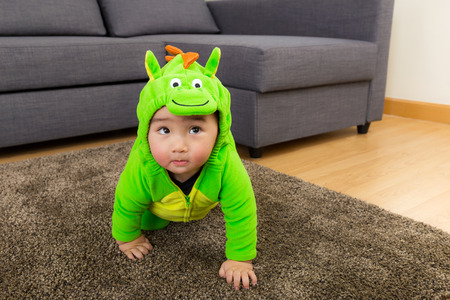 baby crawling: Young baby boy dressed in dinosaur