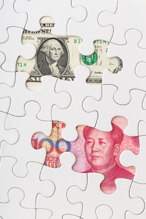 US and Chinese currency as part of puzzle  photo