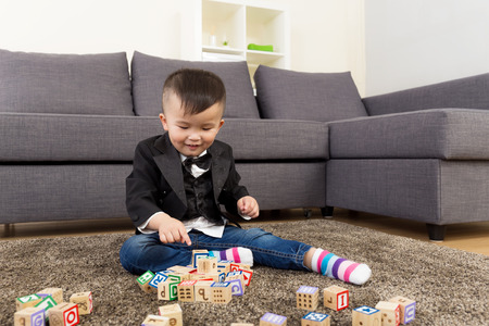 Little boy play wooden toy block at home photo