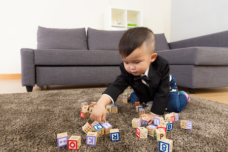 Little boy play toy block at home photo