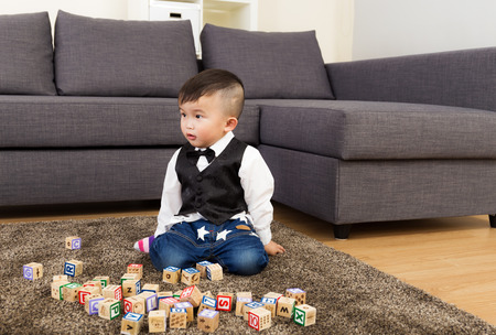 Asian baby boy play wooden block at home photo